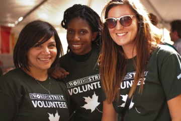 Three festival volunteers smiling at the camera.