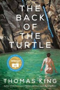 Image Description: Book cover for The Back of the Turtle by Thomas King; it has an illustration of a body of water near some rocky cliffs. We can see the back of presumably a woman standing in the water.