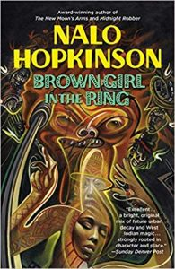Image Description: The book cover for Brown Girl in the Ring by Nalo Hopkinson. The book cover has the author name and book title over a cover showing an African-style illustration of a woman's face, and the faces of figures in the background. Above the woman's face is a monstrous figure .